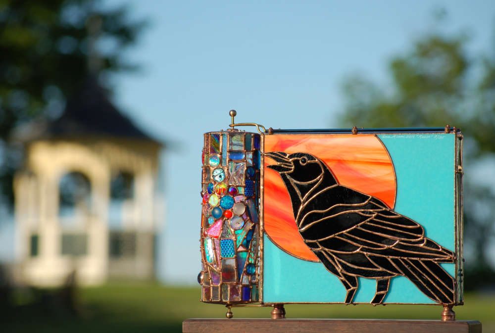 Our 2019 crafts festival promotion design features a stained glass kaleidoscope, Raven, crafted by Sue Rioux Designs with the Laudholm gazebo in the background..