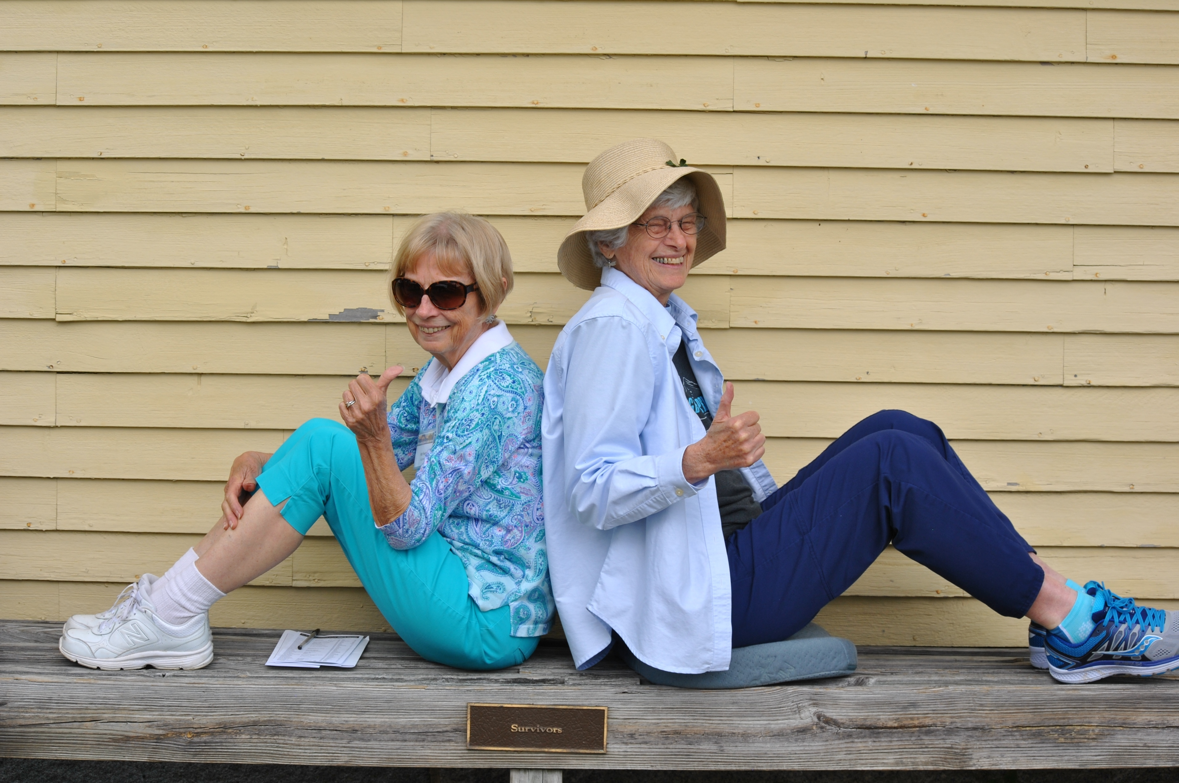 "Pat Frost and Alice Strait give a thumbs up on the ""Survivors Bench."""