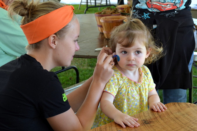 A face painter at work on a cutie