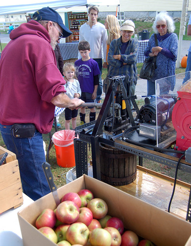 Dan Smith pressed apples for cider as kids and adults look on and wait for samples. 2016 Punkinfiddle.