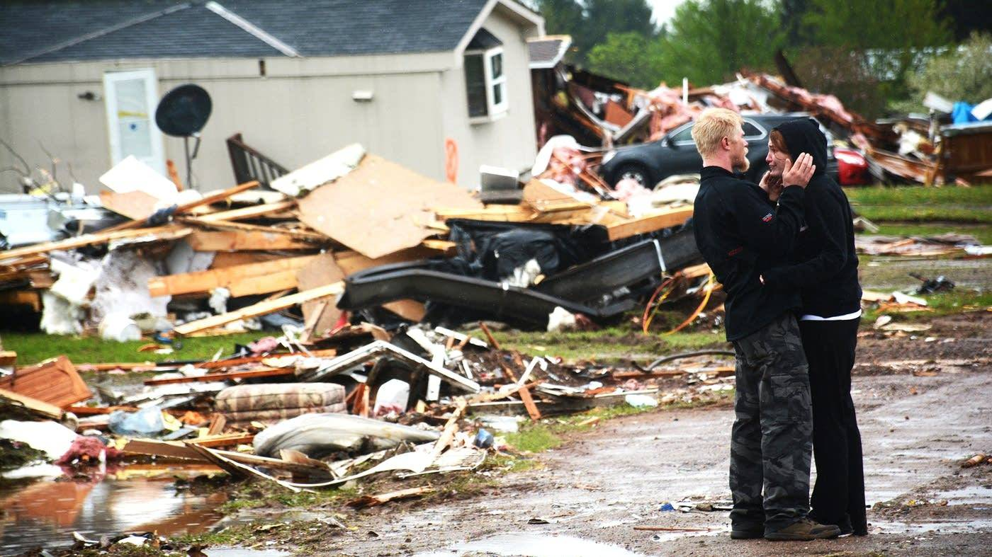 Caption: Ronald Blomberg comforts his fiancee, Marissa Rhoades, amid the devastation from a tornado that struck the Prairie Lake Estates mobile home park near Chetek, Wis., on Wednesday, May 17, 2017. Tim Nelson | MPR News