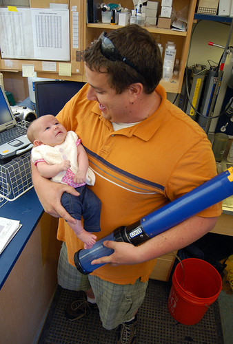 Jeremy Miller holds daughter Camille and water testing instrument in the research lab.