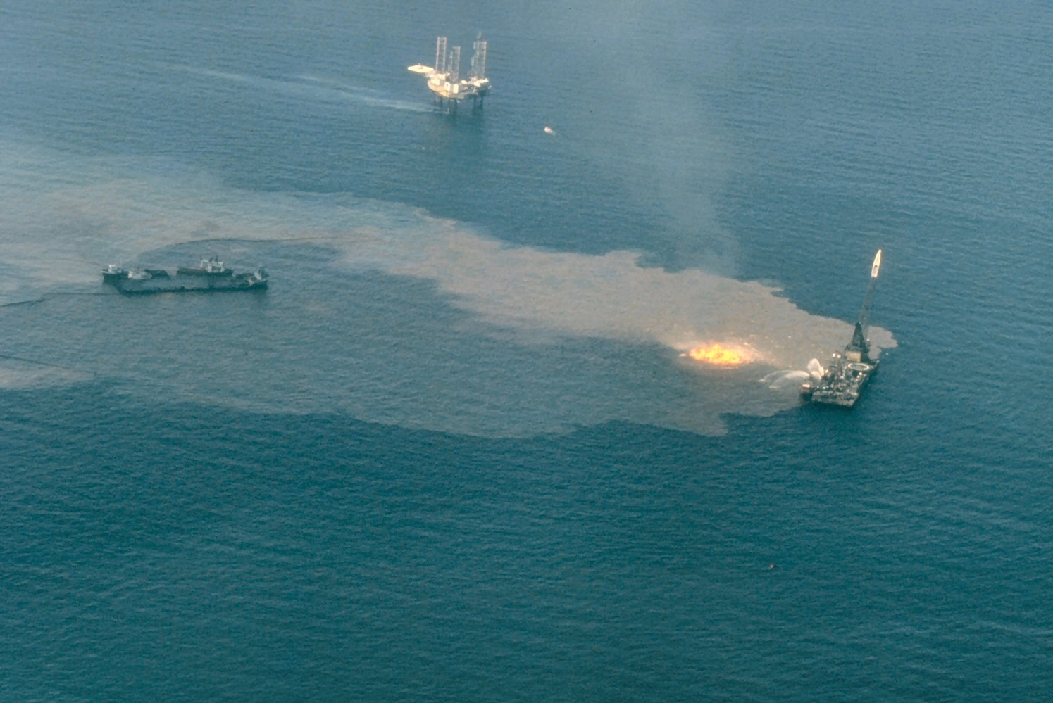 A platform at the site of the Ixtoc-I oil well blowout burns in the Bay of Campeche, Mexico. Public domain image by NOAA.