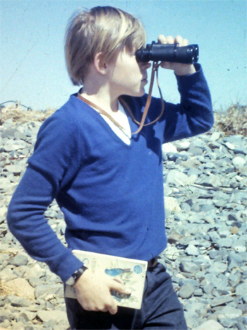 A young me on a Kennebunk beach with binoculars and field guide.