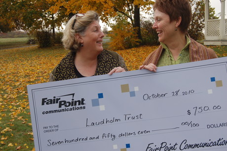FairPoint's Leslie Roberts shares a donation with Laudholm president Diana Joyner